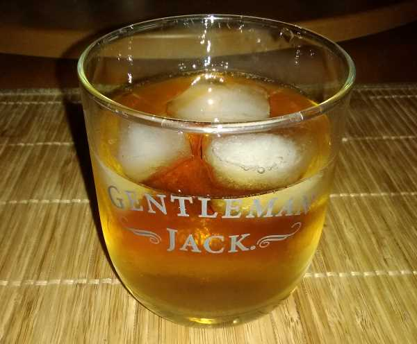 An adult beverage made of Black Velvet Canadian whiskey, their Toasted Caramel flavor infused variety, with ice and water too, in a classy Gentleman Jack glass by the Jack Daniels folks down in Tennessee.