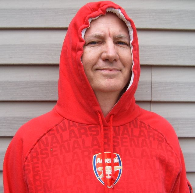 As a member of The Gunners fan club, Chrome Dome Mike Kimbro of Louisville, Kentucky USA is always happy to wear his stylish red hoodie sweat shirt from the Arsenal soccer club of North London, England.
