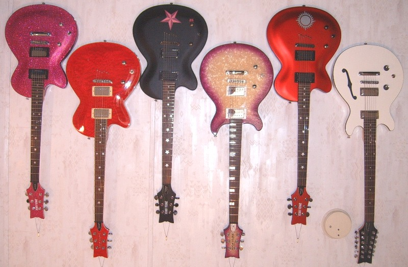 My Daisy Rock Electric Guitar Collection, including (from L to R) the Rock Candy in Atomic Pink, the Rock Candy Special, the Dark Star model of the Rock Candy Custom, the Stardust Elite, the Aztec Goddess model of the Rock Candy Custom, and the Retro-H 12-String guitar.