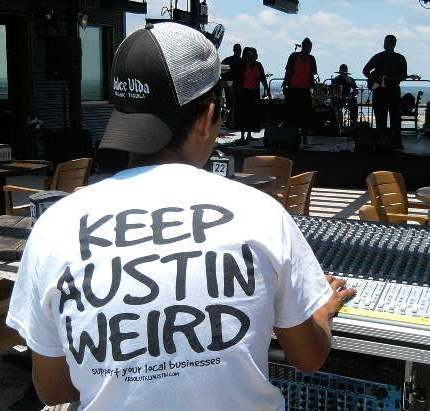 "Photo of young man wearing a ""Keep Austin Weird"" T-shirt while operating a sound console for the gospel group Wesley Bray and the Disciples of Joy, while they were performing at a gospel brunch at an eatery overlooking Lake Travis near Austin, TX."