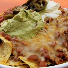Beautiful photo of a supreme nacho dish with guacamole and refried beans, the pinicle of Tex-Mex cuisine.