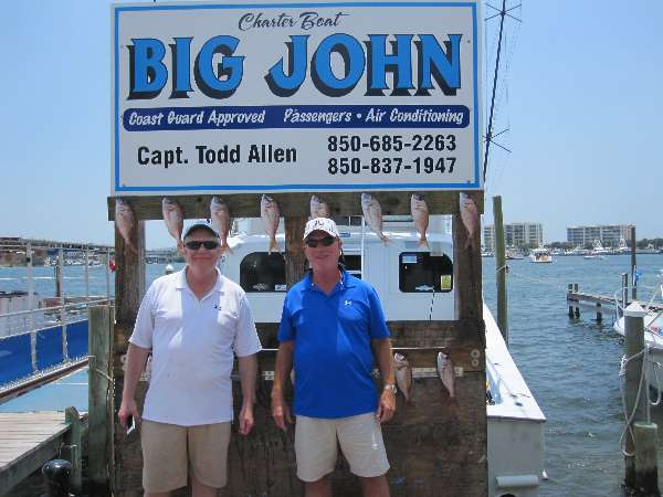 Gary Maxwell and Lee Skaalrud standing in front of the Big John charter boat of Capt Todd Allen which sails out of Destin Harbor near the Emerald Grande at Harborwalk Village.